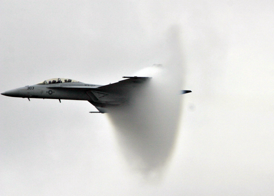 9. An F/A-18F Super Hornet Fighter Jet, November 13, 2004, United States Navy. Pensacola, State of Florida, USA. Reaching the sound barrier, breaking the sound barrier: Flying at transonic speeds (flying transonically) -- speeds varying near and at the speed of sound (supersonic) -- can generate impressive condensation clouds caused by the Prandtl-Glauert Singularity. For a scientific explanation, see Professor M. S. Cramer's Gallery of Fluid Mechanics, Prandtl-Glauert Singularity at <http://www.GalleryOfFluidMechanics.com/conden/pg_sing.htm>; and Foundations of Fluid Mechanics, Navier-Stokes Equations Potential Flows: Prandtl-Glauert Similarity Laws at <http://www.Navier-Stokes.net/nspfsim.htm>. Photo Credit: Photographer's Mate 2nd Class Mark A. Ebert, Navy NewsStand - Eye on the Fleet Photo Gallery (http://www.news.navy.mil/view_photos.asp, 041113-N-4204E-512), United States Navy (USN, http://www.navy.mil), United States Department of Defense (DoD, http://www.DefenseLink.mil or http://www.dod.gov), Government of the United States of America (USA).